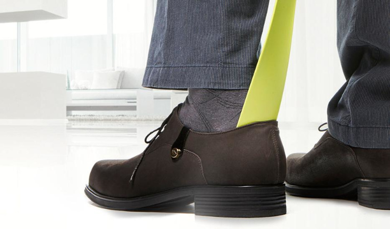 Человек надевает ботинки
